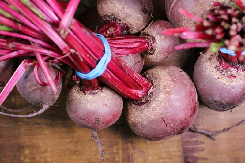 A bunch of uncooked beets.