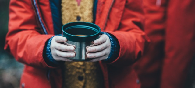 shallow focus photography of person holding soup cup