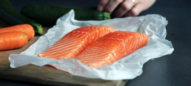 Two pieces of fresh salmon on white paper.